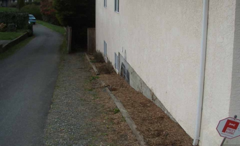 Typical landscaping above foundation level resulting in water entry and wood root